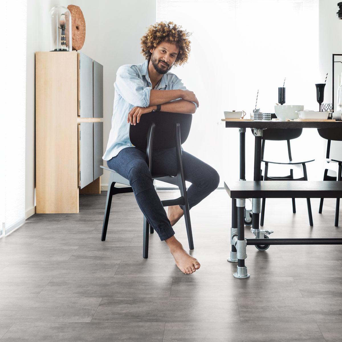 wineo Designboden mit Mann auf einem Stuhl sitzend