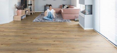 wineo Bodenbelag im Wohnzimmer mit Frau vorm Sofa und Teppich