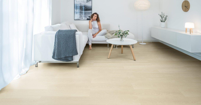 wineo Bodenbelag im Wohnzimmer mit Frau und moderner Einrichtung