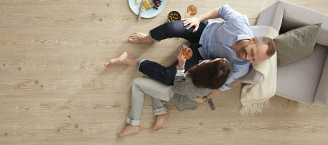 wineo Bodenbelag Holzfußboden Mann Frau Sessel Teller mit Essen Weingläser Wohnzimmer