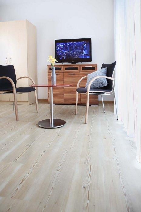 wineo PURLINE Bioboden im Seniorenheim Fernseher Stühle Tisch moderne Einrichtung Holzoptik Fußboden